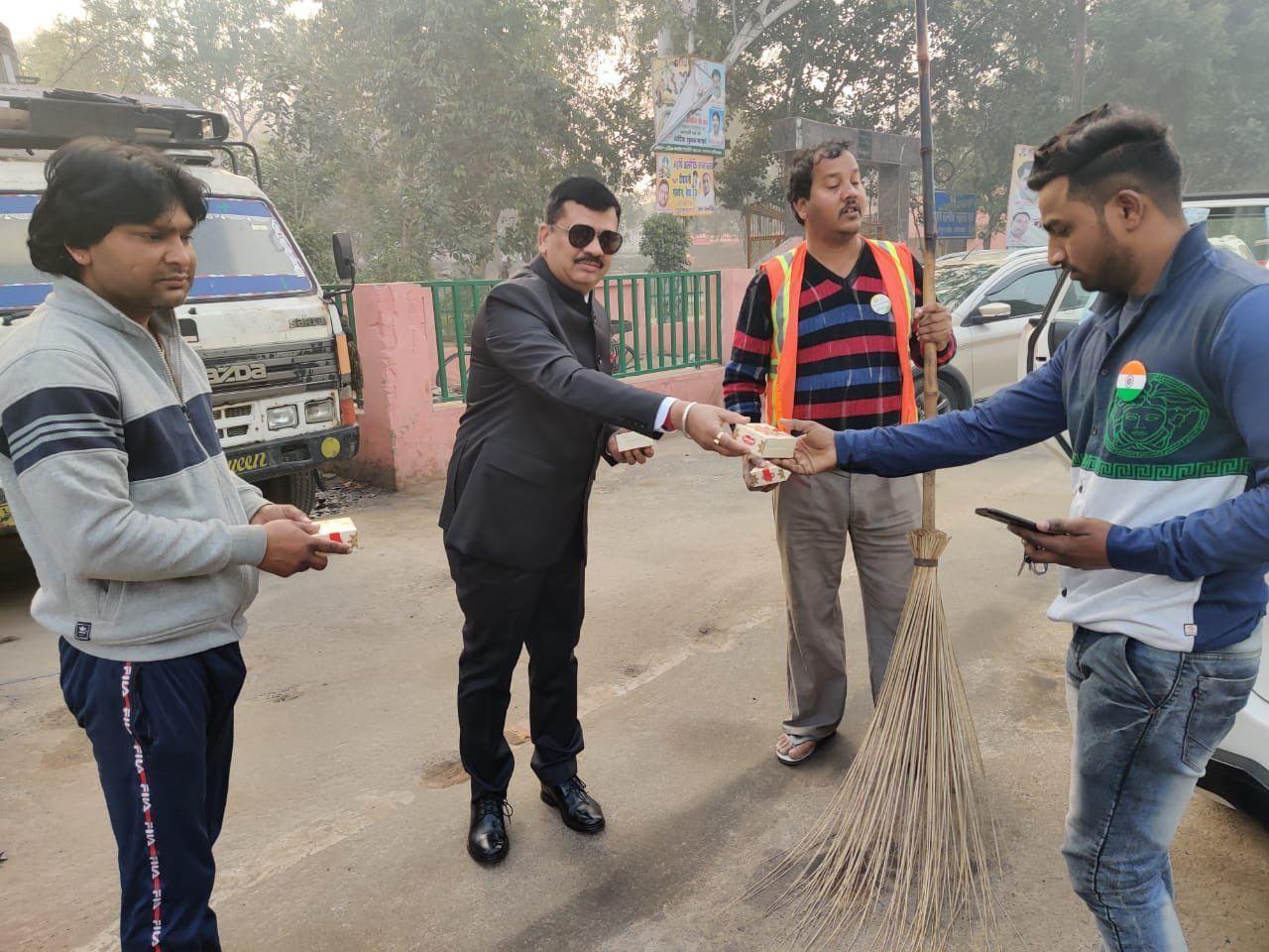 सफाई कर्मचारियों को मिठाई का पैकेट बांटते हुए नगर आयुक्त दिनेश चंद्र सिंह।